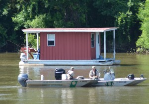 A pair of search boats are shown on the river in front of the houseboat where Eugene Jacobs and his granddaughter loved to go and fish.
