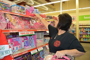 Beth Evans reaches for a stuffed animal to add to the collection box at the Family Dollar in Bristol