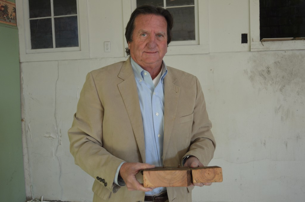 Owner Jim Anders II holding cut timber from the original wooden structure